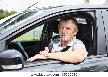 Happy Senior Male With Ignition Key Sitting In Car On Driver Seat And Smiling
