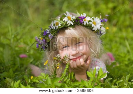 Happy Little Girl In Flowers Wreath Lying On Green Grass
