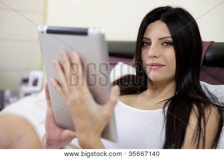 Beautiful Woman In Bed With Tablet Smiling