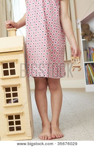 Detail Of Girl Playing With Dolls House In Bedroom