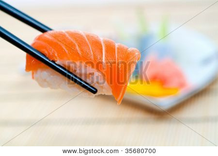 Sushi with chopsticks, With a back background