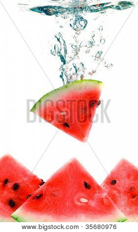 watermelon are falling in water with a big splash