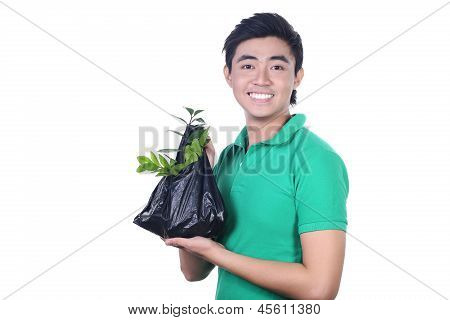 Young Asian man carrying a plastic trash bags