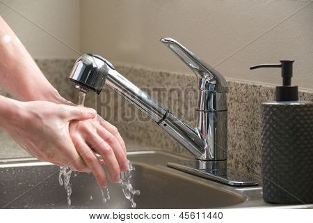 Washing hands in the kitchen sink