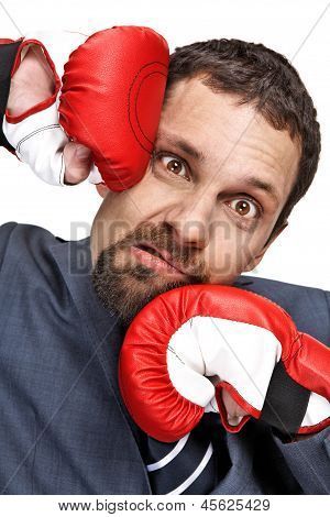 Close-up young businessman struck in the face by hands in boxing gloves