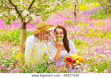 Young happy family having picnic on floral field in spring garden, eating healthy organic food, holiday and vacation concept