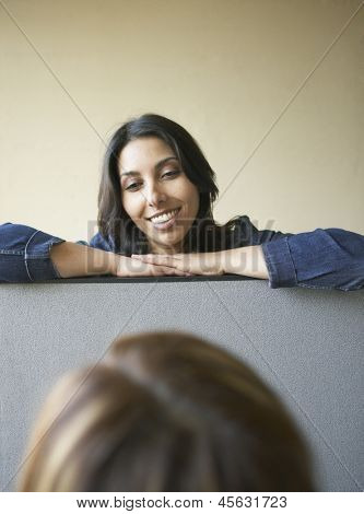 Businesswoman talking to colleague over cubicle wall