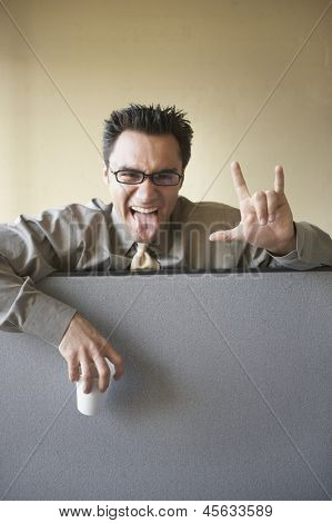 Businessman gesturing over cubicle wall