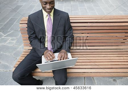 Businessman sitting on bench with laptop on his lap