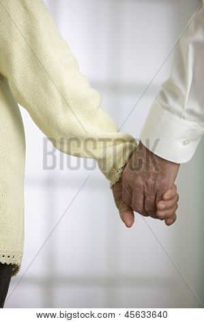 Close up of elderly couple holding hands