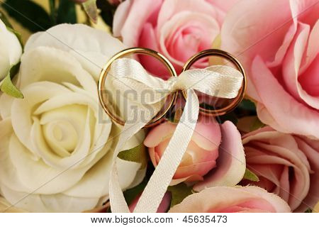 Wedding rings tied with ribbon on rose background