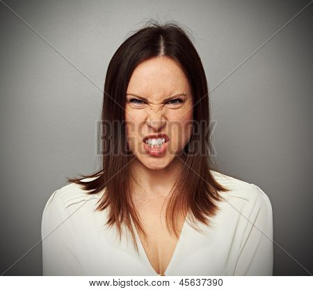 mad woman baring her teeth over grey background