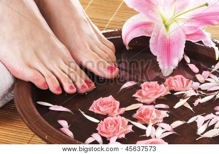 Spa background with a beautiful legs, flowers, petals and ceramic bowl
