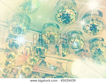 Many disco balls on ceiling in a nightclub