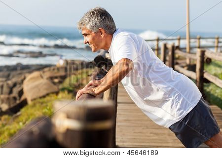 fit senior man exercising at the beach in the morning