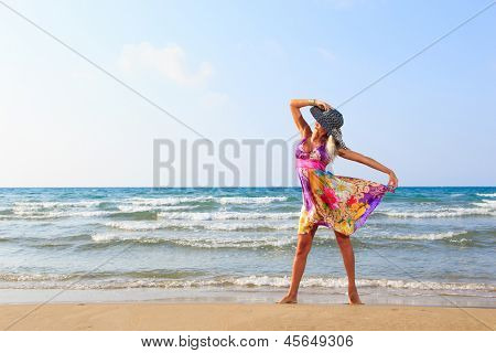 Beautiful young woman in summer dress on the beach