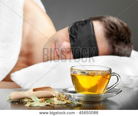 Man With Sleeping Mask Sleep On A Bed, Cup Of Herbal Tea In The Foreground
