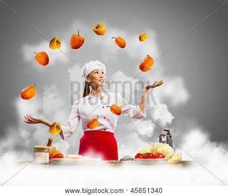 malabarista mulher asiática cozinhar contra a cor de fundo