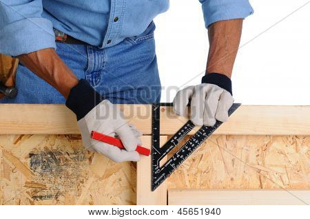 Closeup of a carpenter climbing using a framing square to mark lines on the studs of a wall he is building. The man is leaning over the wall and is not recognizable.