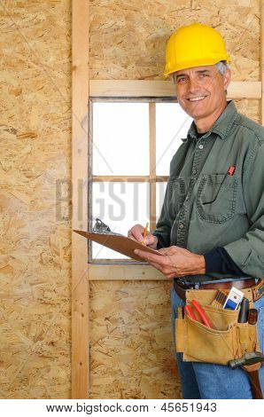 A middle aged contractor standing in new construction writing on a clip board. Man is wearing jeans, work shirt, tool belt and a hard hat, and smiling at the camera. Vertical Format.