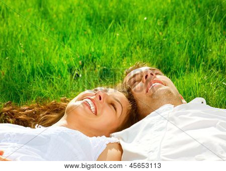 Happy Smiling Couple Relaxing on Green Grass. Park. Young Couple Lying on Grass Outdoor