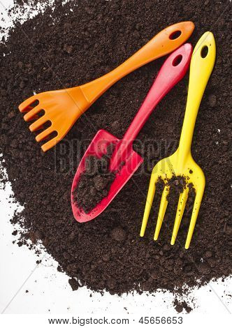Colorful gardening tools in the soil surface corner border isolated on white background