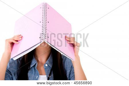 Frustrated female student with a notebok on her head - isolated over white