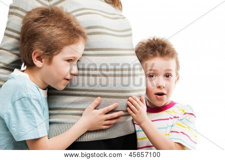 Pregnancy and new life concept - two little child boy brothers touching or bonding pregnant mother abdomen