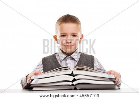 Little smiling child boy reading education books at desk