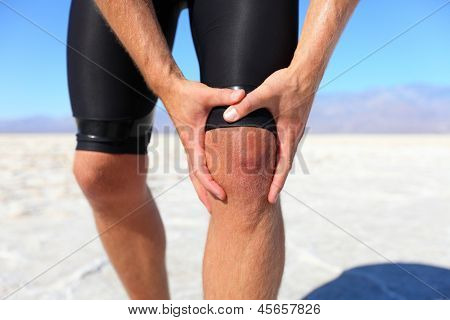 Injuries - sports running knee injury on man. Male runner with pain, maybe from sprain knee. Close up of legs, muscle and knee outdoors.