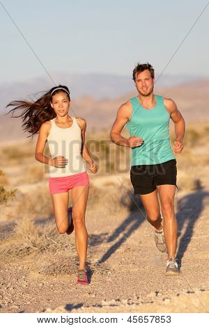 Running couple - runners jogging on trail run path outside in beautiful nature. Asian woman runner and Caucasian male fitness sport model jogger training together for cross-country marathon.