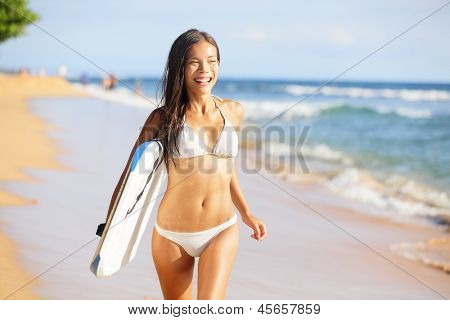 Happy beach people - woman surfer having fun laughing running with bodyboarding surfboard. Beautiful sports bikini model cheerful on summer travel vacation. Water sports image of Asian Caucasian girl.