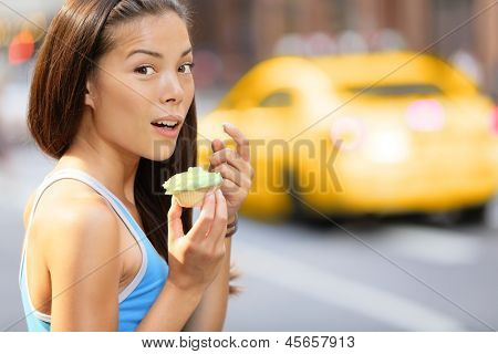 Cupcakes - woman caught eating cupcake snack after running training. Funny image of fitness girl surprise shocked looking at camera eating unhealthy food. Beautiful woman in New York City, Manhattan.