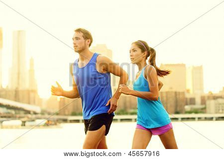 City running couple jogging outside. Runners training outdoors working out in Brooklyn with Manhattan, New York City in the background. Fit multiracial fitness couple, Asian woman, Caucasian man.