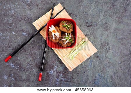 Asian meatballs, ganhished with pea shoots and radish julienne, in a red bowl on bamboo tray with chopsticks, against natural slate background. Space for your text