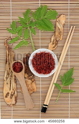 Chinese herbal medicine of saffron spice and angelica herb root with leaf sprigs over bamboo background.