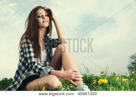 Portrait of young beautiful brunette woman  sitting on grass