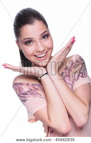 young casual woman looking very excited at the camera and smiling hile holding her head on her palms