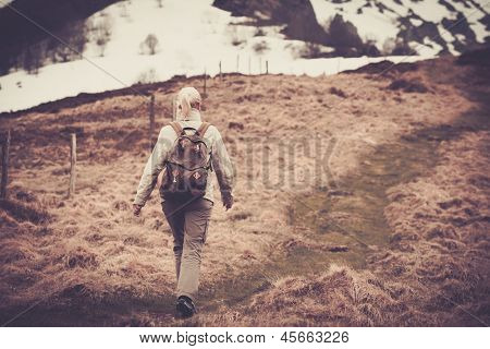 Young woman hiker with rucksack  walking in mountains
