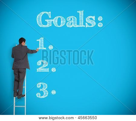 Businessman writing goals on a giant blue wall helped by a ladder