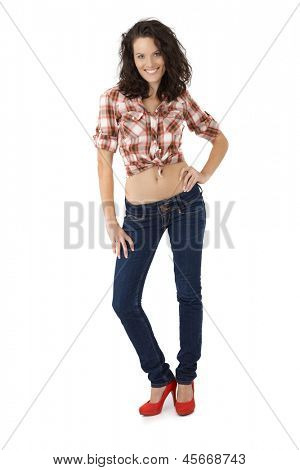 Sexy woman in shirt jeans and red high heel shoes posing, cutout on white.