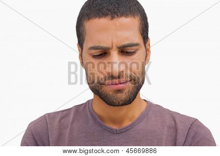 Handsome man frowning and looking down on white background