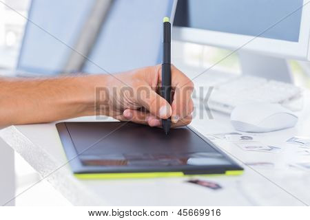 Male hands using graphics tablet on white desk