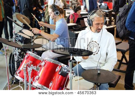 MOSCOW - SEP 22: People play on the electronic drum kit with headphones on XVIII International Exhibition of Music Moscow 2012 in Sokolniki on September 22, 2012 in Moscow, Russia.