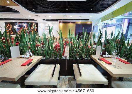 Halle des gemütlichen japanisches Restaurant mit quadratischen Tischen und grünen Blättern.