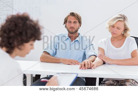 Psychologist taking notes while couple speaks