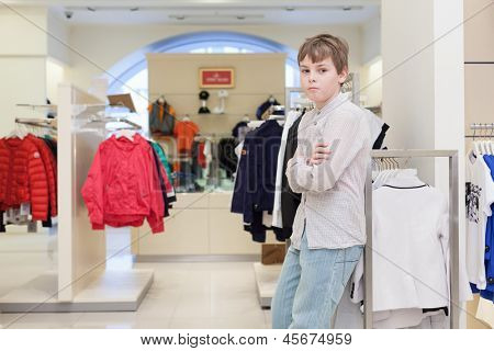 The boy chooses modern clothes in the childrens clothing store