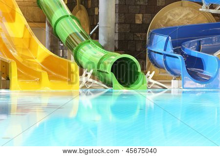 Big multi-colored water slides and pool in indoor aquapark. Yellow, green and blue slides.