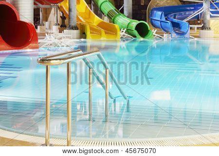 Metal railings, pool and multi-colored water slides in indoor aquapark.