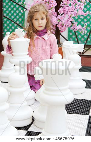 Thoughtful little girl in pink sits among large white chess pieces in park.